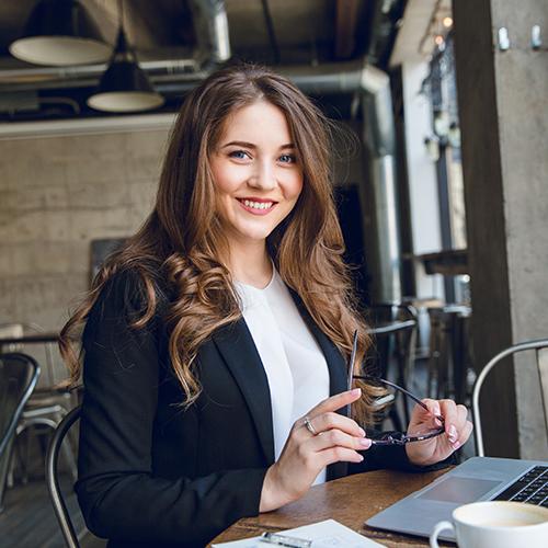 Uśmiechnięta kobieta z laptopem i okularami